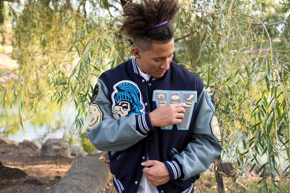 Colorado Springs Senior Photography Widefield High School senior adjusting the pins on his varsity jacket in front of a willow tree Stacy Carosa Photography
