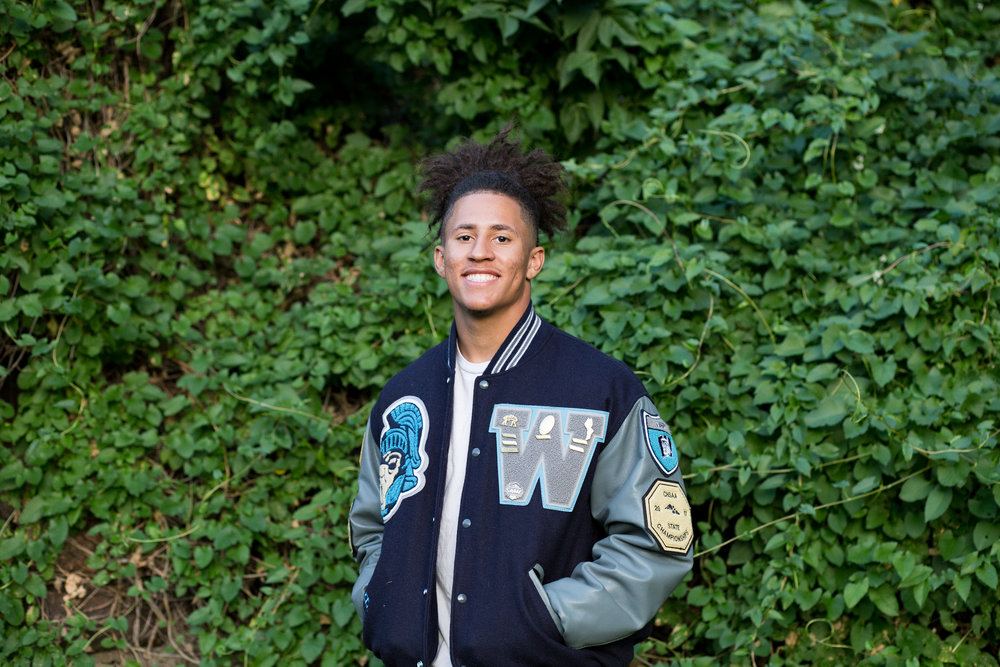 Senior boy standing in front of a wall of ivy in Downtown Colorado Springs for his senior photos in his varsity jacket from Widefield High School Stacy Carosa Photography