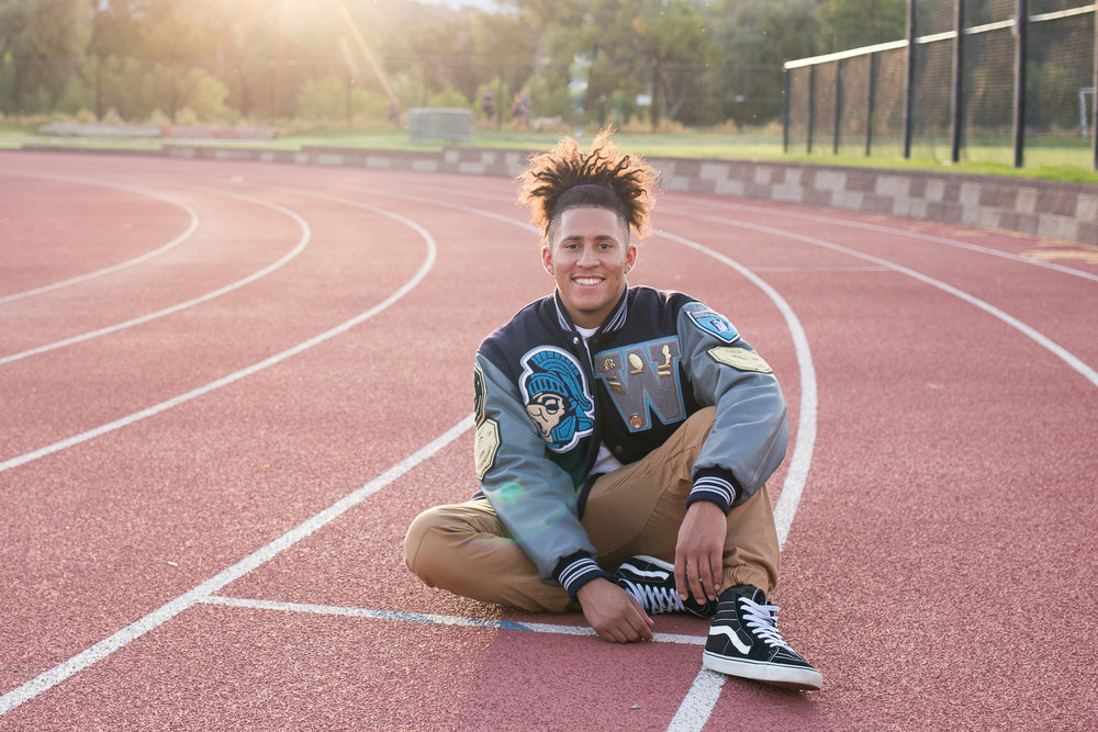 Senior smiling while sitting on a track wearing his varsity jacket and smiling at the camera. Stacy Carosa Photography Colorado Springs senior photography