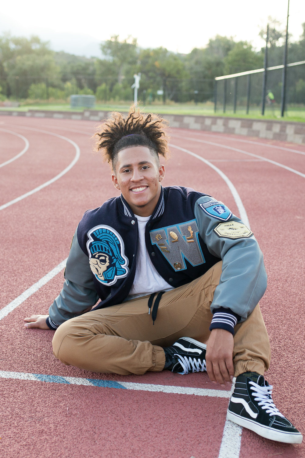 Colorado Springs Senior Photography Widefield high school senior in varsity jacket sitting on a running track