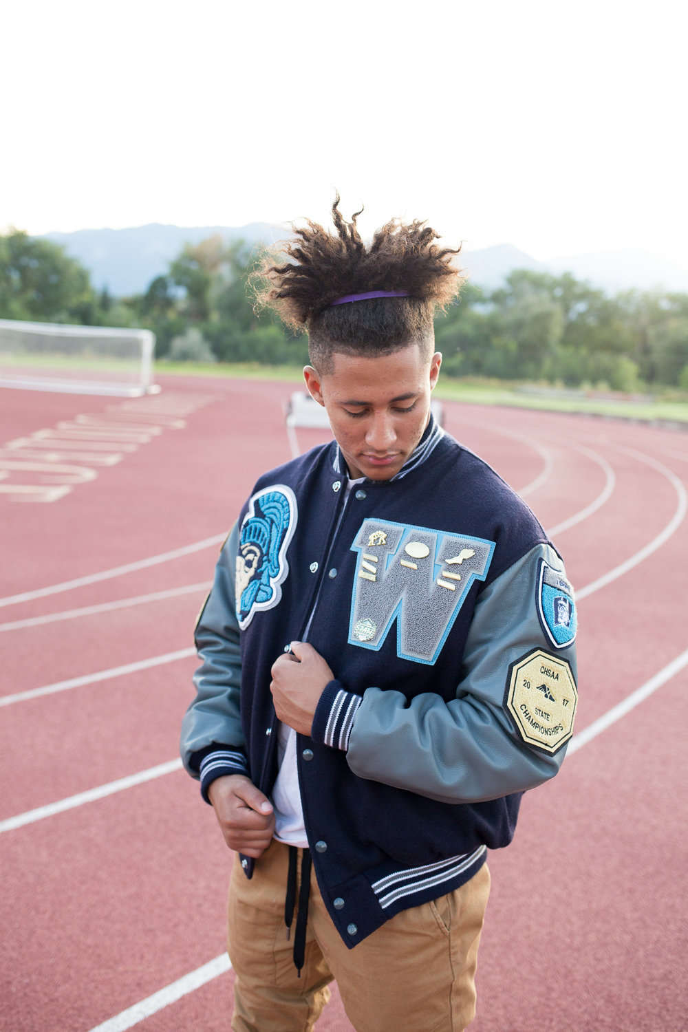 Senior in varsity jacket looking at his badges and pins while standing on a track. Stacy Carosa Photography Colorado Springs senior photography