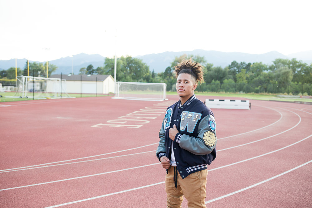 Senior standing on a track holding his varsity jacket while looking at the camera seriously Stacy Carosa Photography