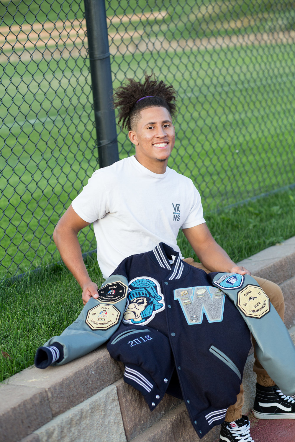 Widefield High  School senior sitting and holding his varsity jacket for his Colorado Spring senior photo session Stacy Carosa Photography