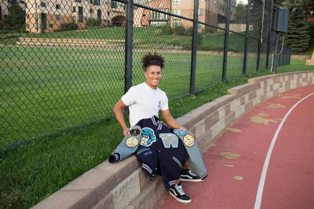 Senior boy sitting on the edge of a track holding his varsity jacket while looking at the camera. Stacy Carosa Photography Colorado Springs Senior Photography