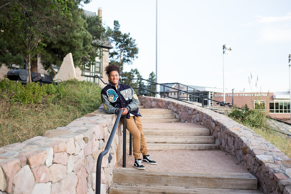Senior standing on stairs leaning against the stone wall in his varsity jacket Stacy Carosa Photography Colorado Springs senior photos