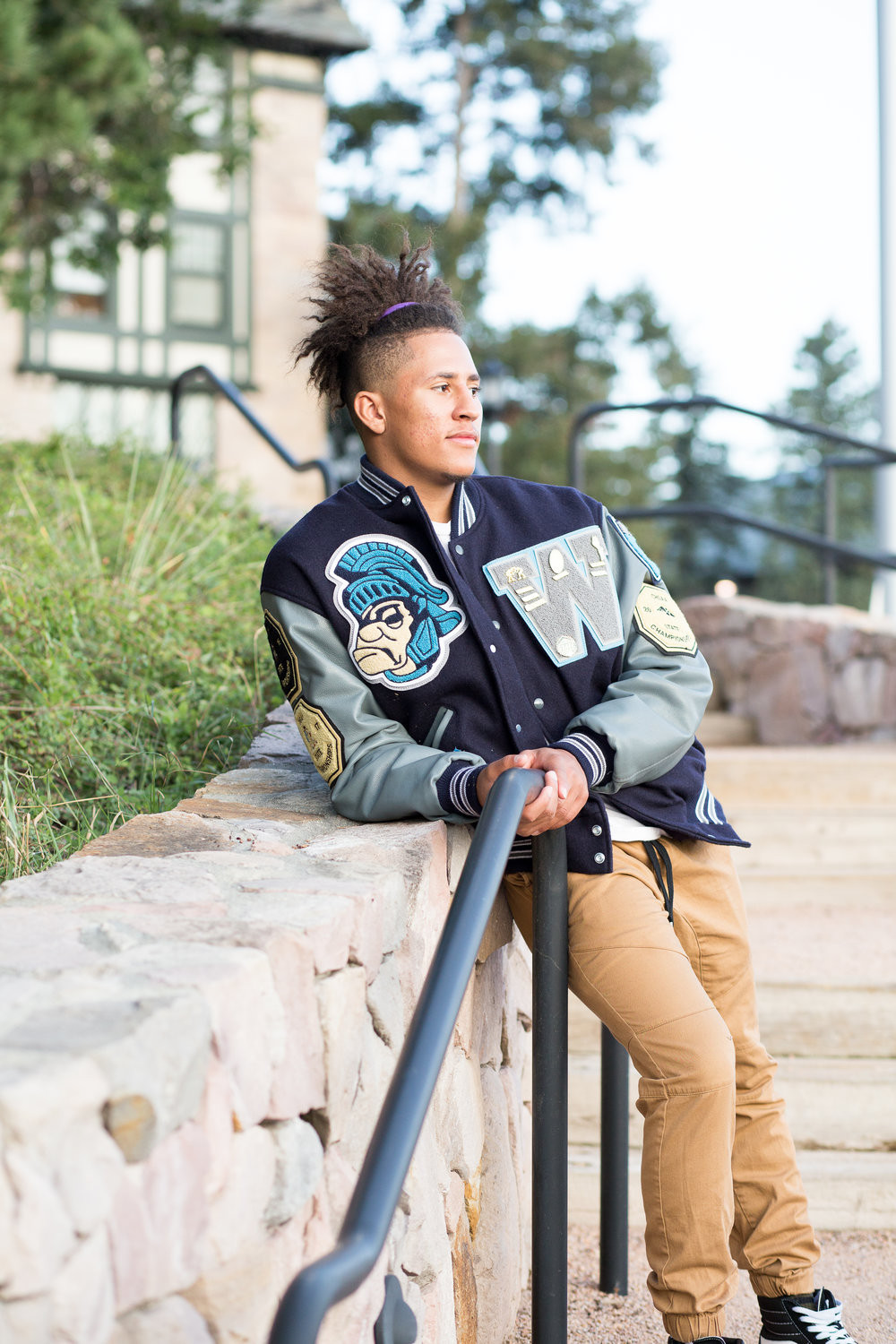 Colorado Springs high school senior leaning against a stone wall on the Colorado College campus looking into the sun Stacy Carosa Photography Colorado Springs senior photography