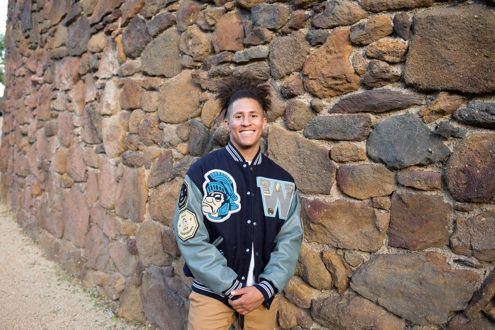 Colorado  Springs senior photo session downtown leaning against big stone wall in varsity jacket Stacy Carosa Photography