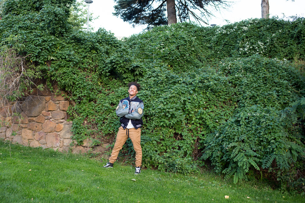 Widefield High School senior in varsity jacket standing in front of a wall of ivy for senior photos Stacy Carosa Photography Colorado Springs