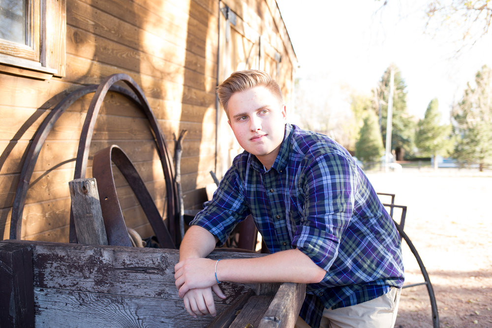 Senior session at Rock Ledge Ranch of St. Mary's boy leaning against crate and looking at camera Stacy Carosa Photography Colorado Springs