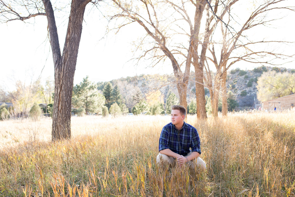 Senior boy sitting among the tall grasses against a tree in Rock Ledge Ranch in Colorado Springs Stacy Carosa Photography