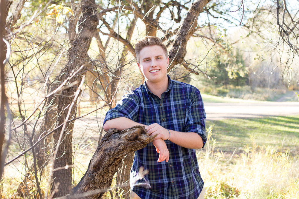 Senior boy with elbow leaning on a downed tree and smiling at the camera at Rock Ledge Ranch Colorado Springs senior session Stacy Carosa Photography