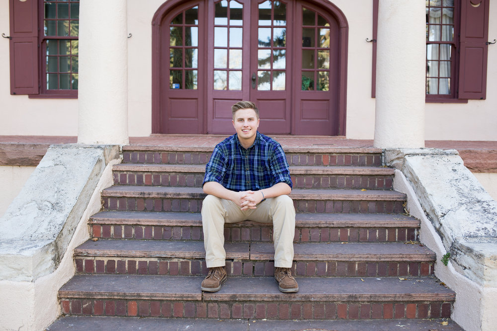Senior session at Rock Ledge Ranch boy sitting on house steps with hands folded together Rock Ledge Ranch Stacy Carosa Photography Colorado Springs