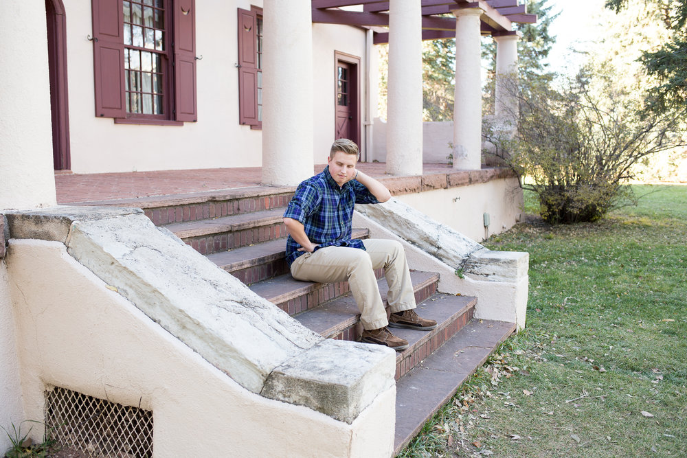 Colorado Springs senior photos at Rock Ledge Ranch senior sitting on stairs with hand on neck Stacy Carosa Photography