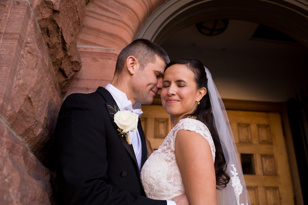 Standing in the arc doorway of the First Baptist Church in Colorado Springs is a groom putting his forehead on his brides temple Stacy Carosa Photography Colorado Springs Winter Wedding