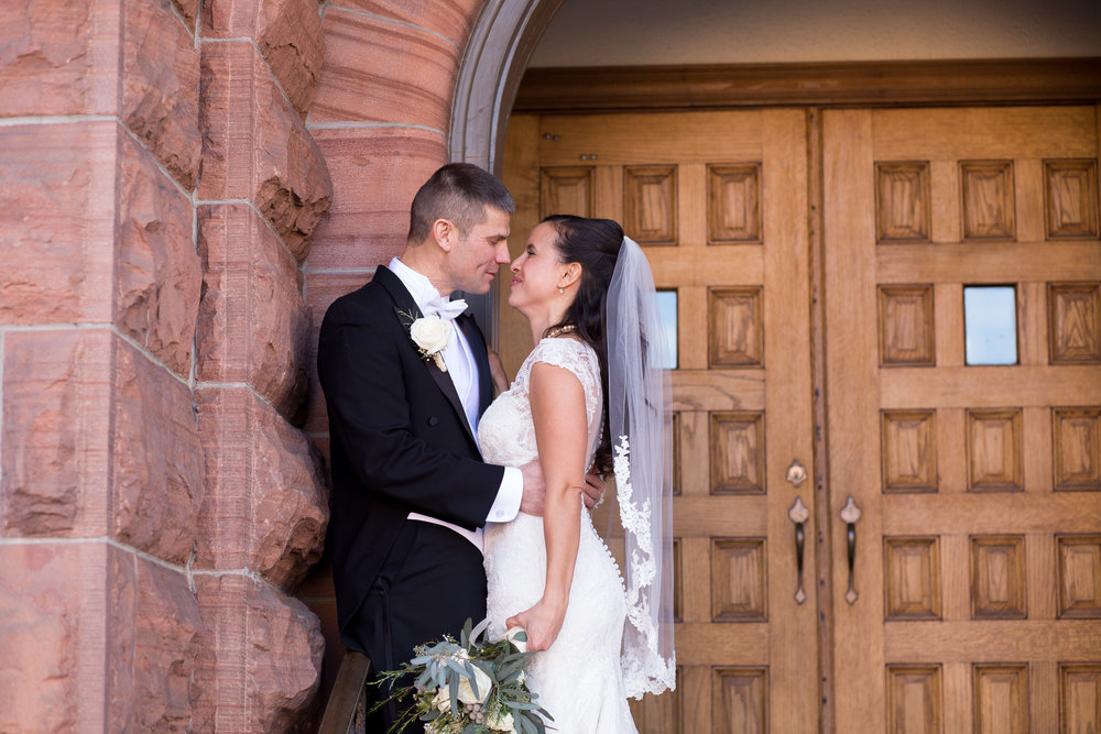 Wedding couple leaning against each other in church door way at First Baptist Church in Colorado Springs Stacy Carosa Photography