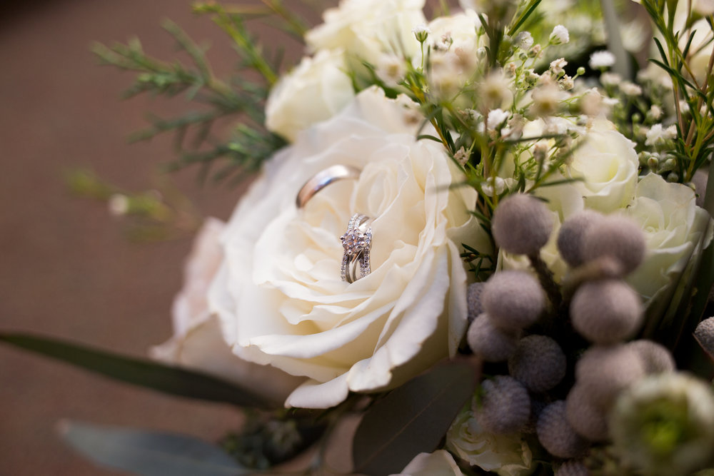 White flowers in a bridal bouquet with wedding rings sitting in a rose Stacy Carosa Photography Colorado Springs Winter Wedding