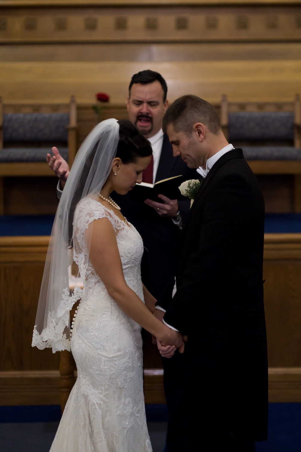 Bride and groom taking a blessing during their wedding at First Baptist Church in Colorado Springs Stacy Carosa Photography