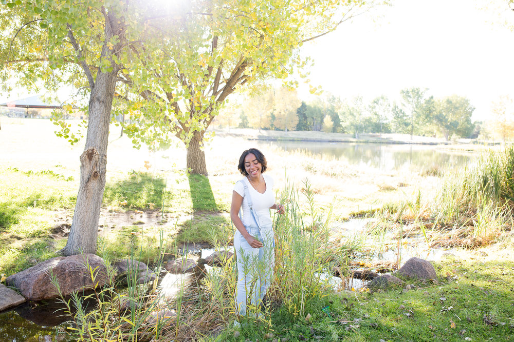 Beautiful morning light coming through tree and highlighting senior girl standing in the tall grasses at Fountain Creek Regional Park for senior photo Stacy Carosa Photography