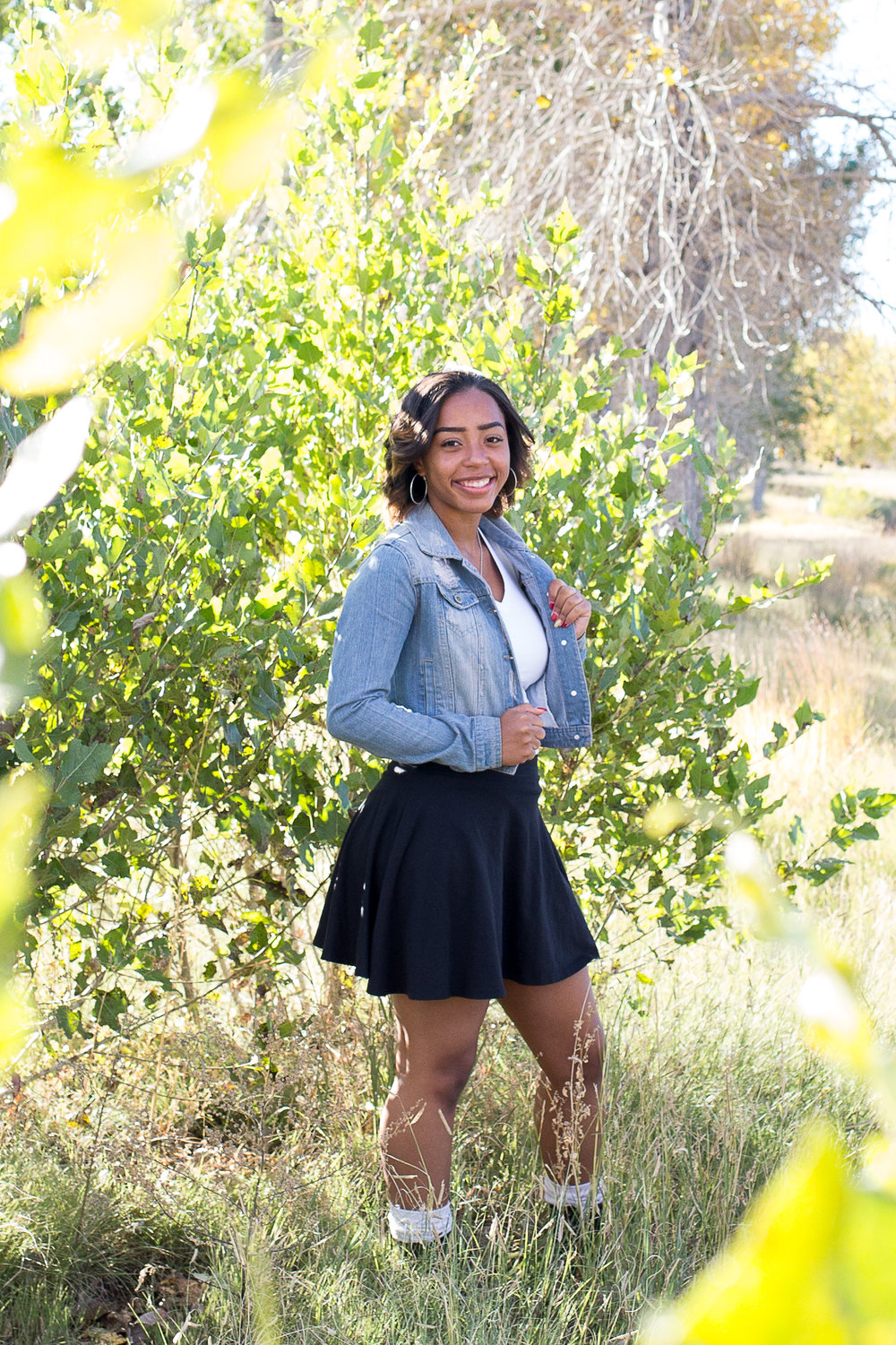 Girl standing among the green trees holding her jean jacket for her senior portraits in Fountain Creek  Regional Park Stacy Carosa Photography Colorado Springs Senior Photos