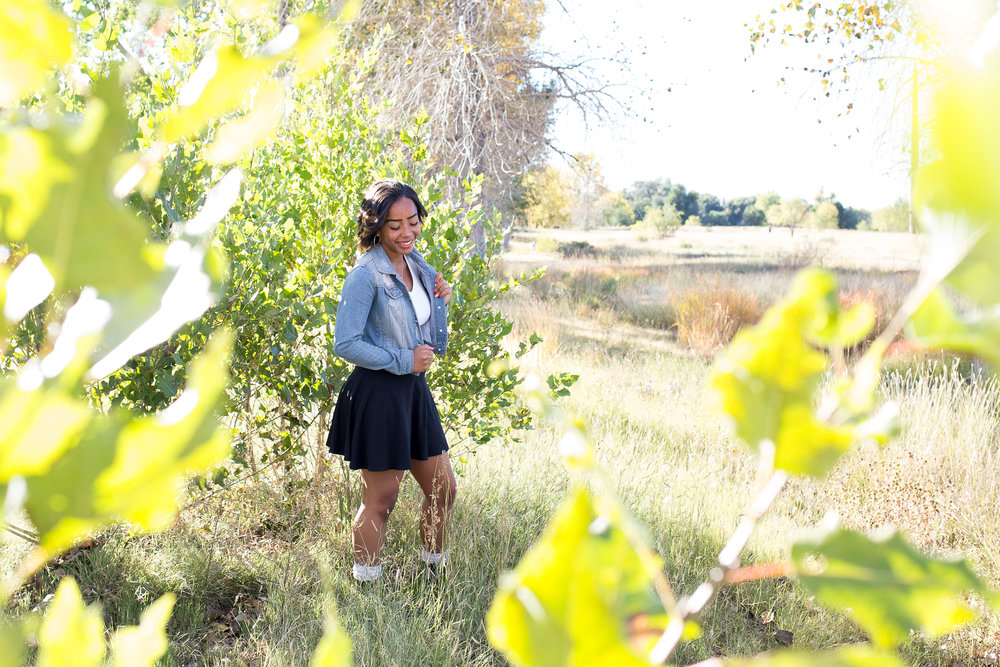 Girl standing by green trees with leaves in the foreground at Fountain Creek Regional Park Widefield High School Senior Stacy Carosa Photography