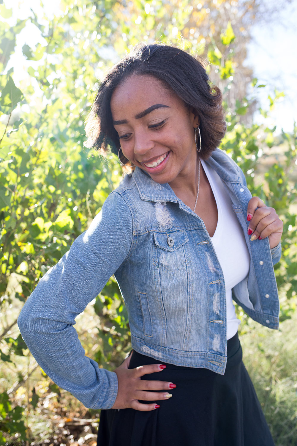Widefield High School Senior holding jean jacket and looking over her shoulder at Fountain Creek Regional Park in Colorado Springs, CO Stacy Carosa Photography