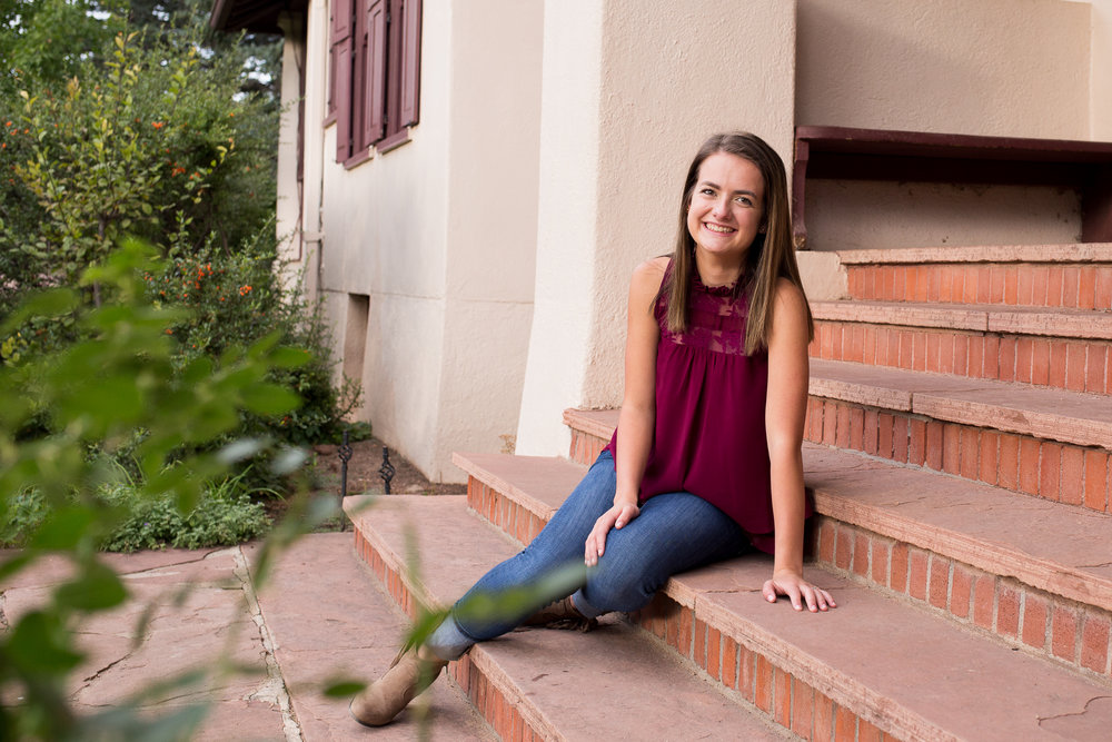 Leaning on stairs on a porch at Rock Ledge Ranch in Colorado Springs for Senior Photo Session Stacy Carosa Photography Colorado Springs Senior Photographer