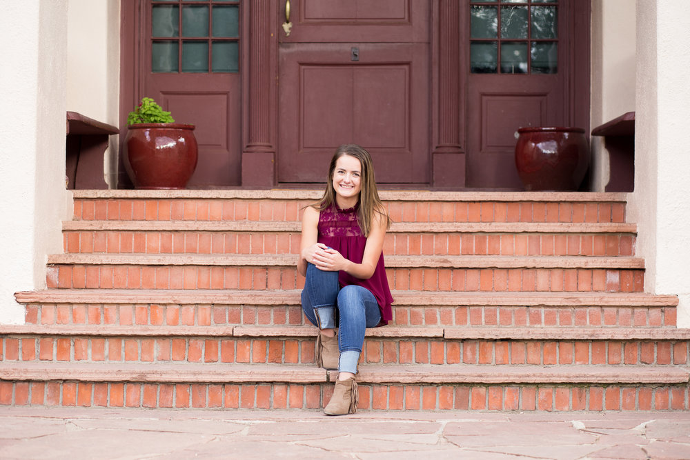 Girl sitting on stairs of a house at Rock  Ledge Ranch in Colorado Springs for her senior photo session Stacy Carosa Photography Colorado Springs Senior Photographer