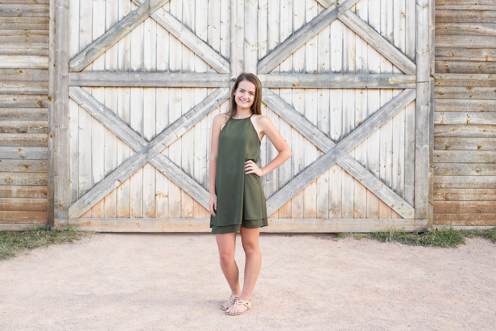 Girl standing in front of barn at Rock Ledge Ranch in Colorado Springs for her Senior Photos | Stacy Carosa Photography