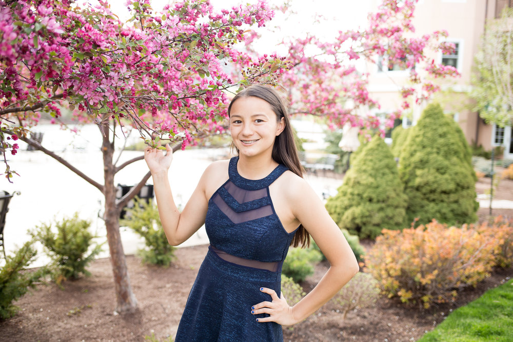 Girl standing by pink spring flowers on tree for her senior session Colorado Springs Senior Portrait Photographer | Stacy Carosa Photography | Colorado Springs Senior Photography | Denver Senior Photography