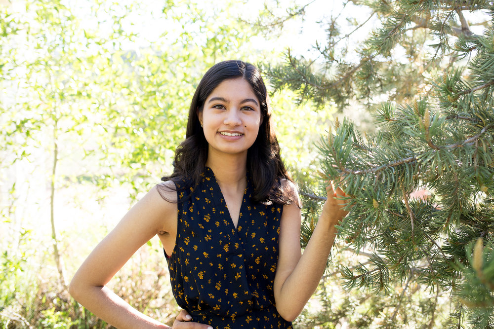 Colorado Springs Senior Photography at Rock Ledge Ranch Stacy Carosa Photography Girl standing near a green pine tree holding on to a brand and smiling at camera