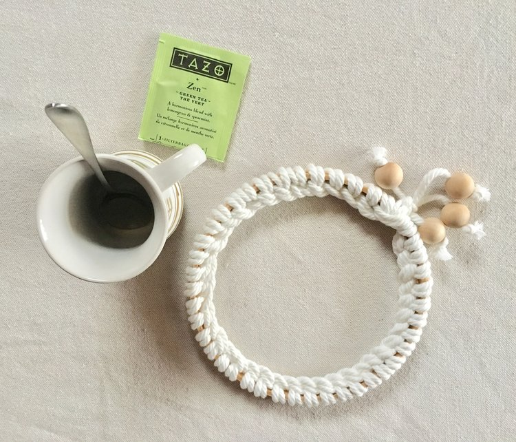 Our hygge trivet is hand knit with wood accents, like this tiny wooden beads. It's most hygge when it's sitting next to my favorite mug -- from my great-grandma -- and cup of Zen tea.