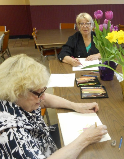 Residents of Washington Manor render spring flowers in colored pencil.