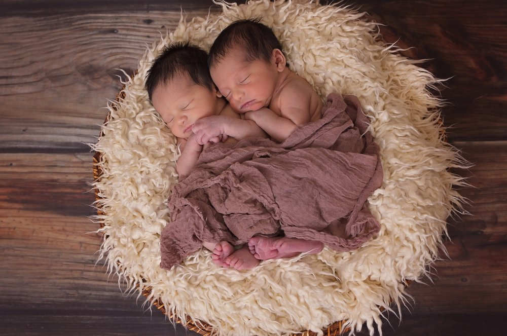 Newborn twins snuggling under a blanket on a faux fur [Rising Tide Women's Whole Life Wellness]