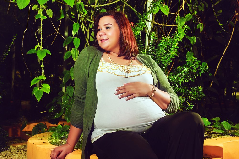Pregnant woman sitting on a bench with plants in the background [Rising Tide Women's Whole Life Wellness]
