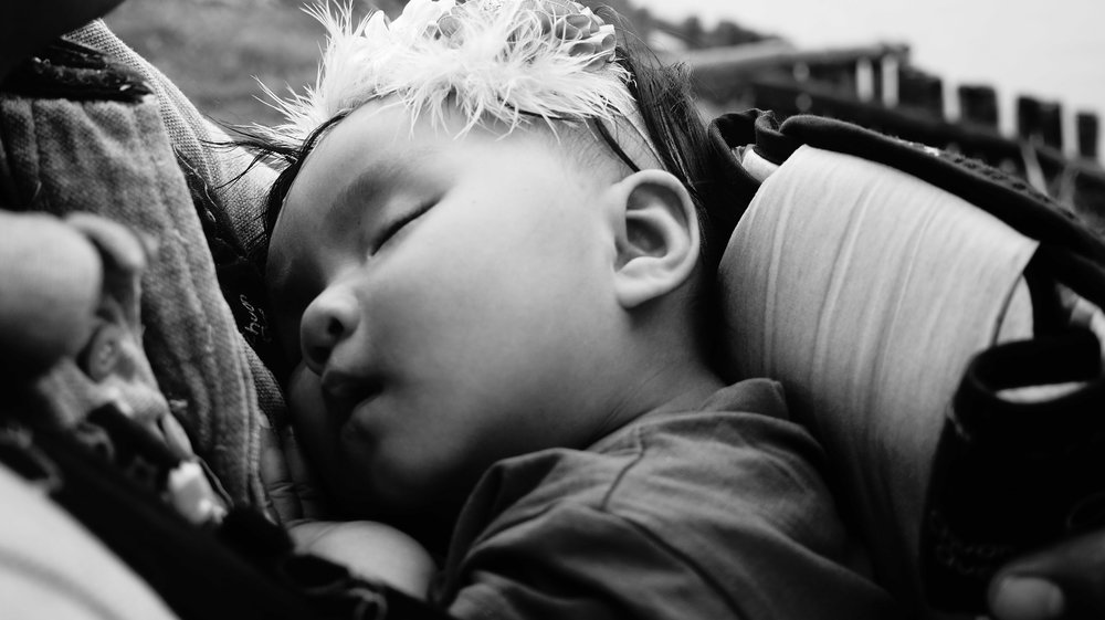 Relaxed baby sleeping in parent's arms [Rising Tide Women's Whole Life Wellness]