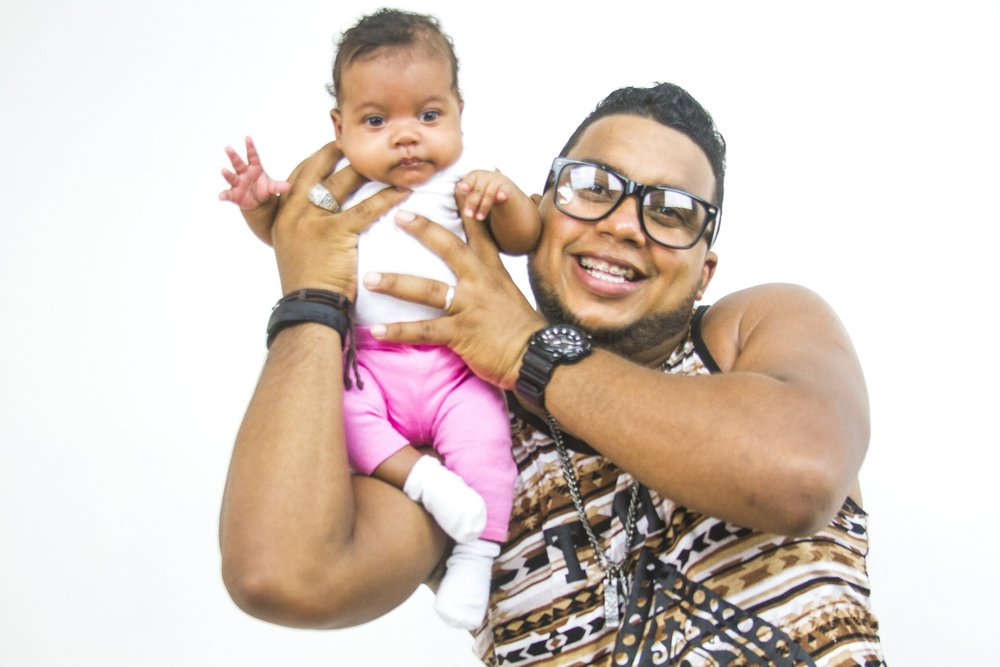 Latino Dad with glasses holding a baby on his shoulder and smiling [Rising Tide Women's Whole Life Wellness]