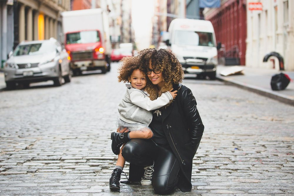 mom holding small child on a cobblestone street. both are smiling [Rising Tide Women's Whole Life Wellness]