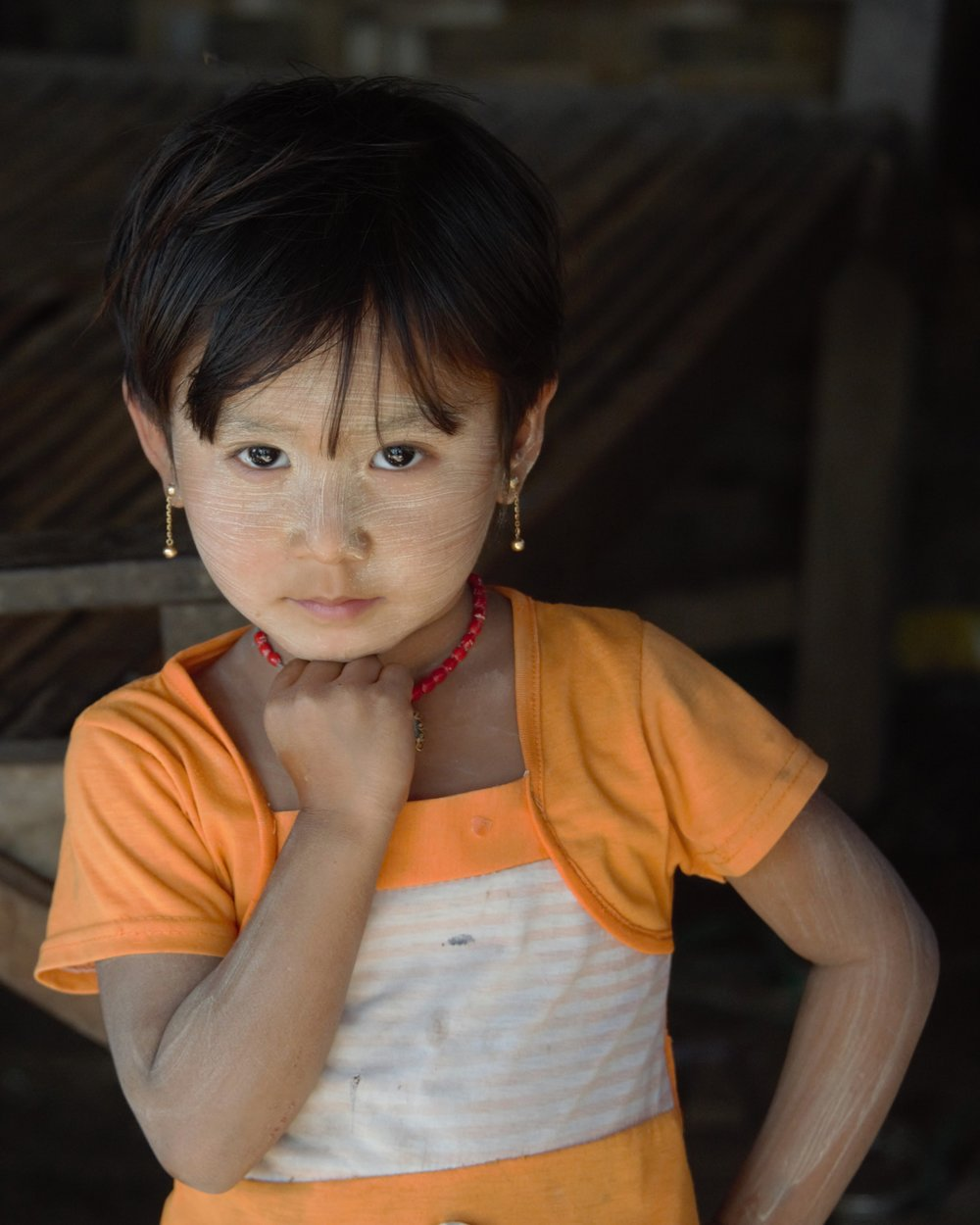 Young village girl showing off her tanaka makeup, Myanmar