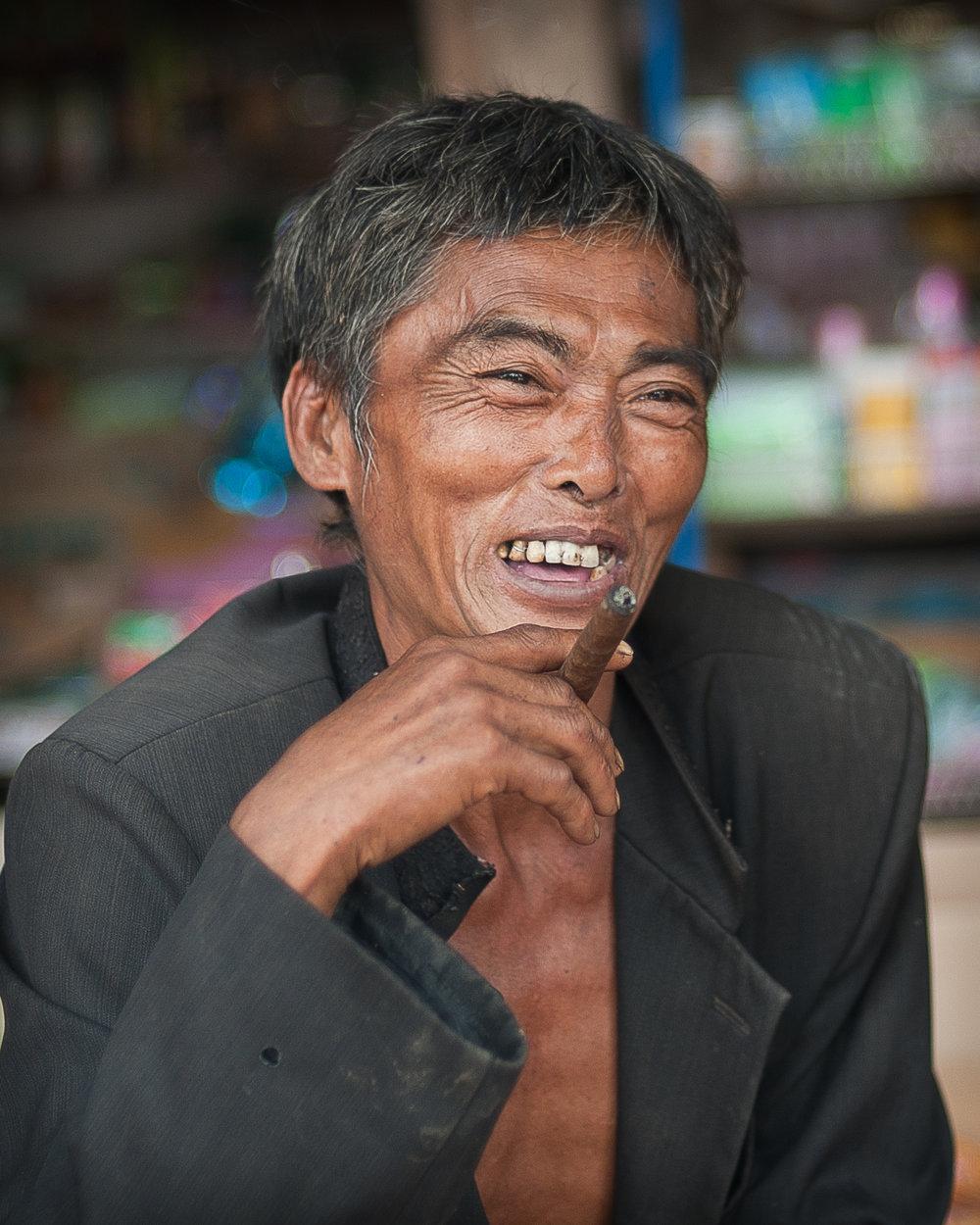 Village Chief enjoys a cigar, small village, Laos