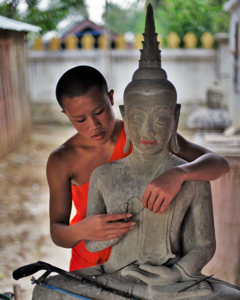 Monk building Buddha statue