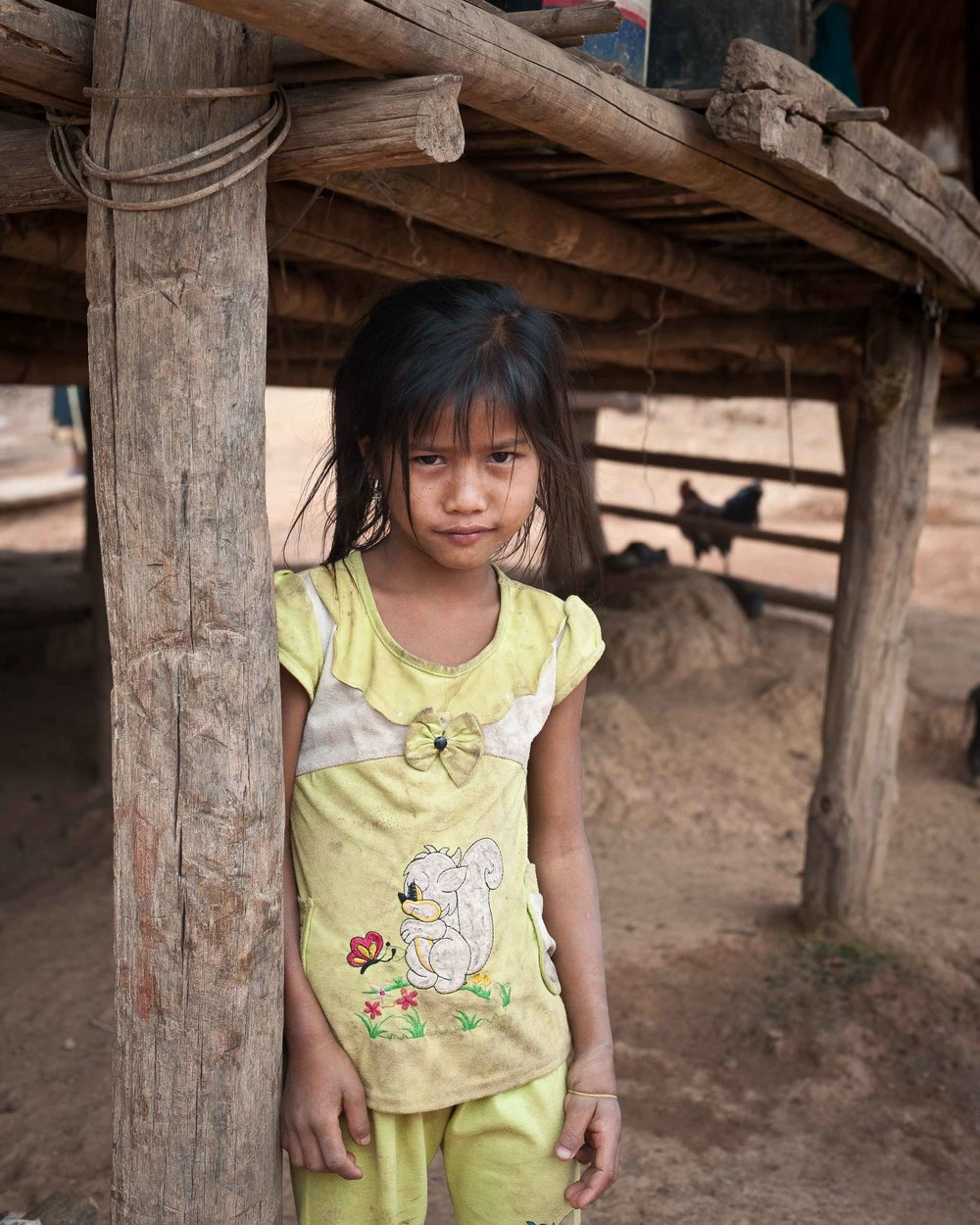 Village girl under family hut, remote Laos
