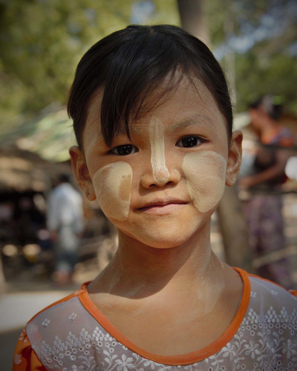 Young girl showing off her tanaka makeup, Bagan, Myanmar
