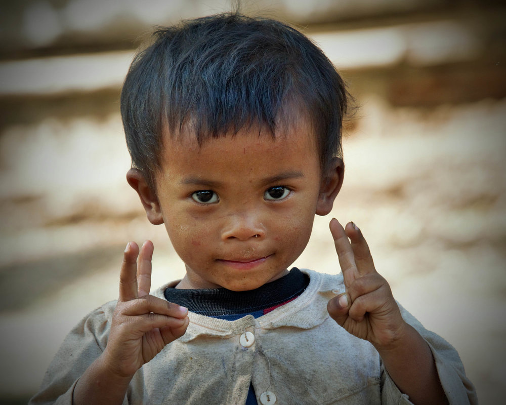 Young boy gives peace sign, Bagan, Myanmar