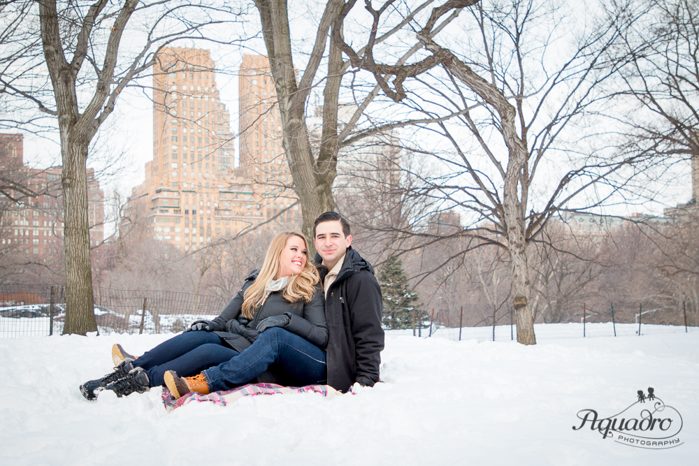 Engaged Couple smiling sitting in the snow in Central Park