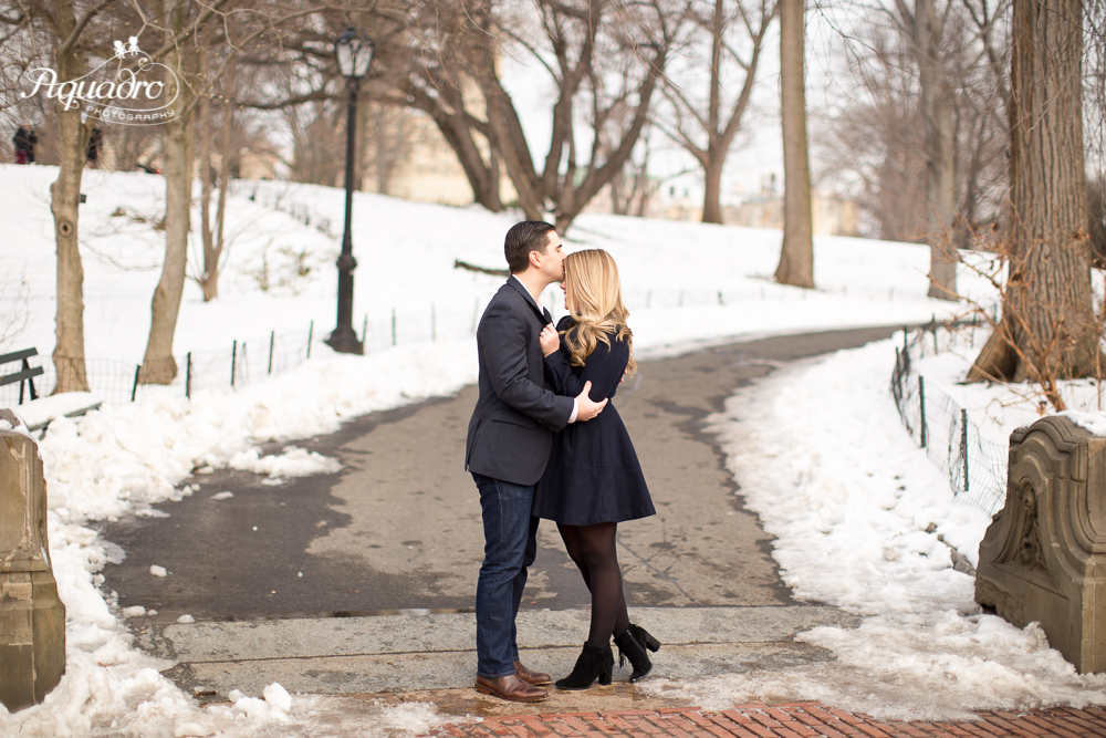 engaged couple share an intimate embrace in snowy Central Park
