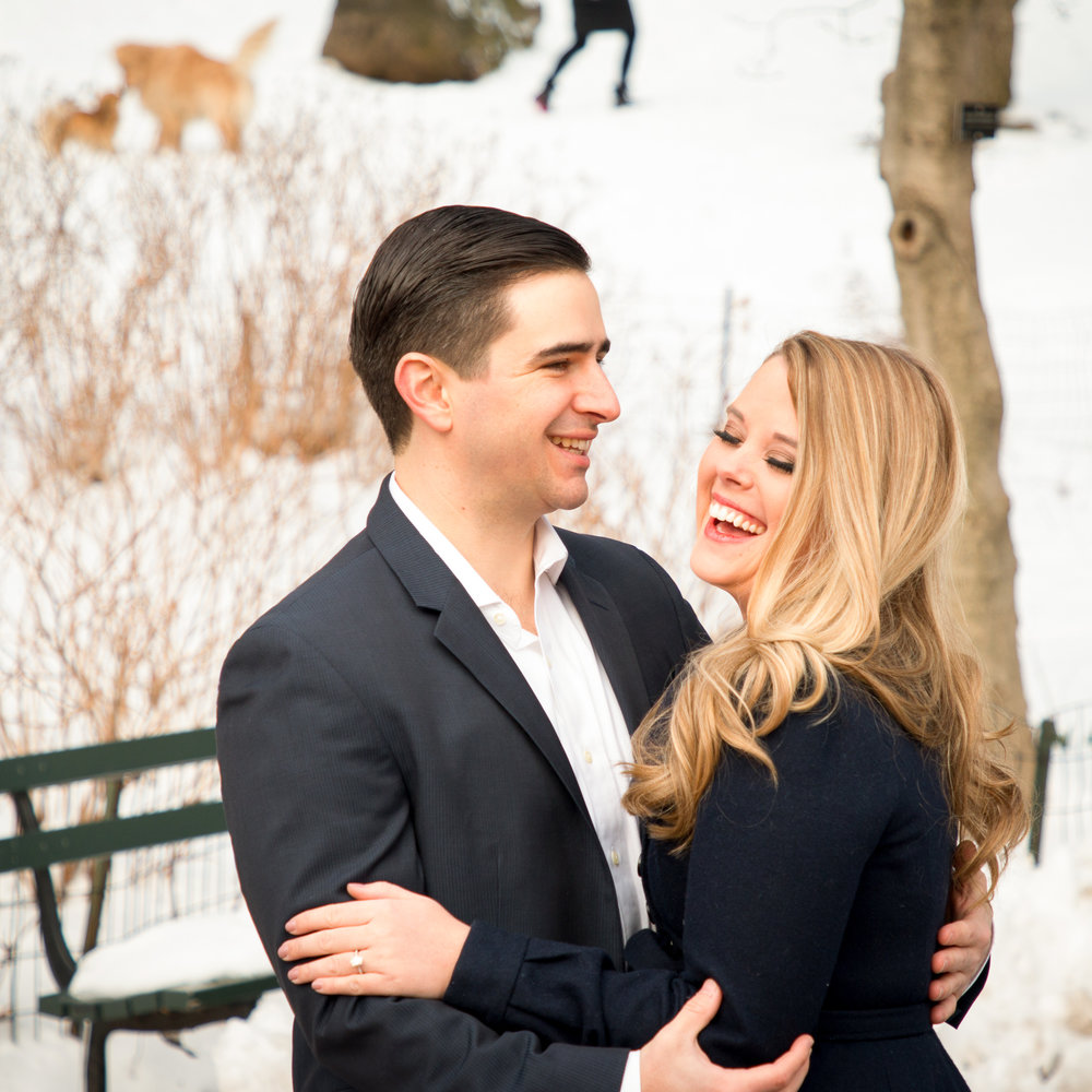 engaged couple laughing in snowy Central Park