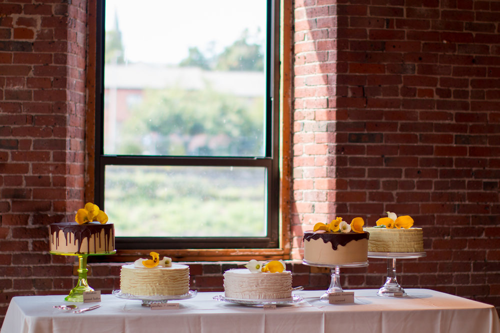 pretty cake table against brick wall