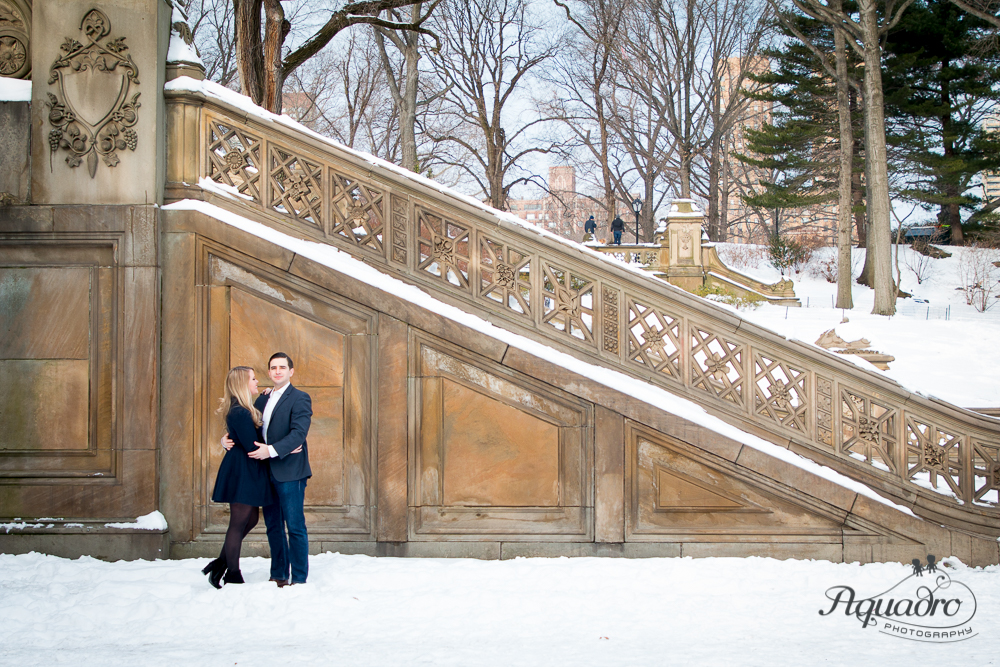 engaged couple embrace by snowy Bethesda Terrace