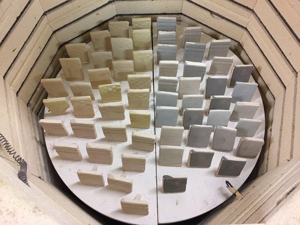 Kiln shelves full of student glaze test tiles.