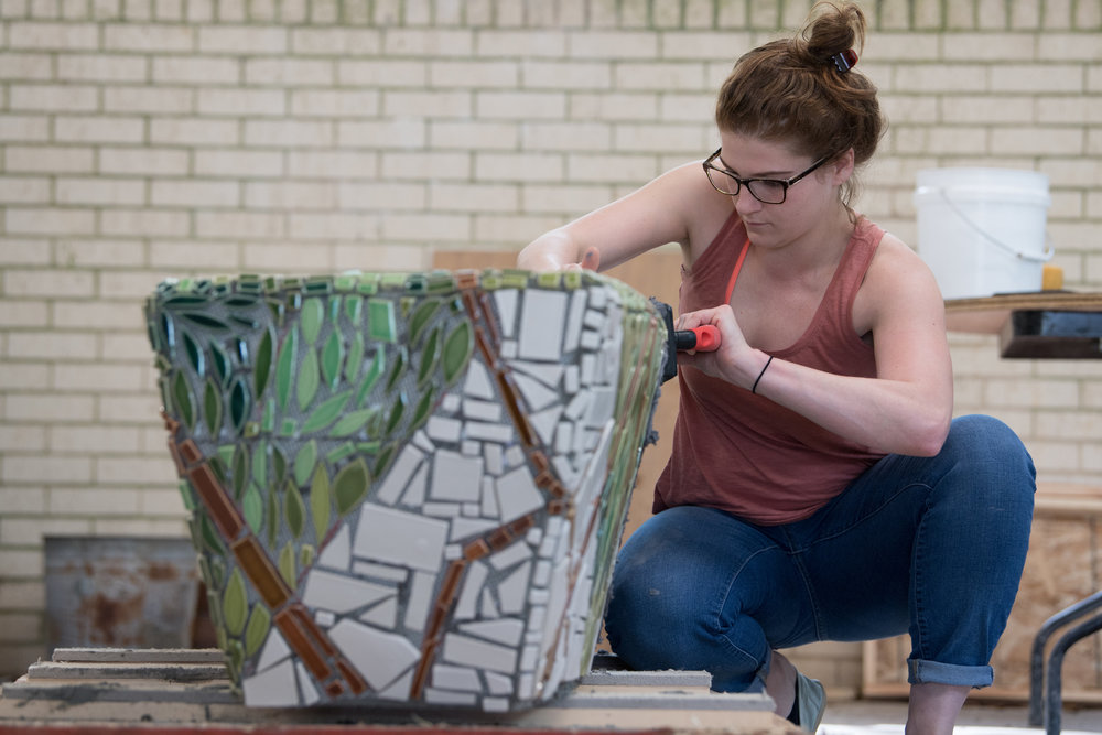 A student grouting the bench.  Photo by Michael Spooneybarger
